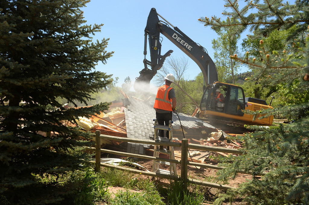 . LYONS, CO - MAY 27: Crews with Ecoos Environmental and Disaster Restoration work on demolishing a home in Lyons that was damaged by last years flood, May 27, 2014.  (Photo by RJ Sangosti/The Denver Post)