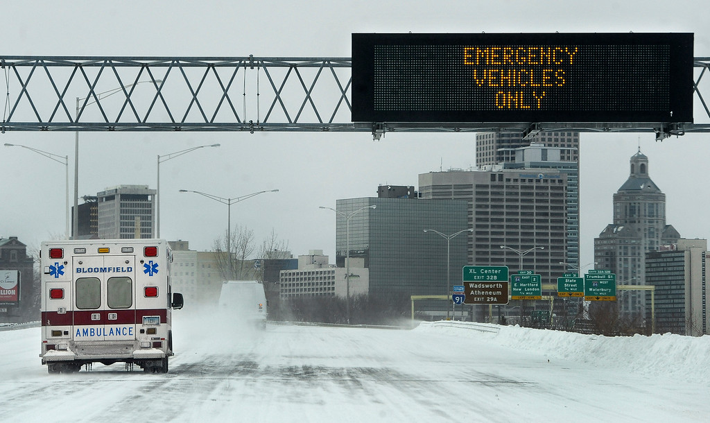 . An ambulance travels on Interstate 91 toward the city, Tuesday, Jan. 27, 2015, in Hartford, Conn. A major winter storm dropped a foot of snow or more over much of Connecticut, hitting hardest in the eastern part of the state.   (AP Photo/Jessica Hill)