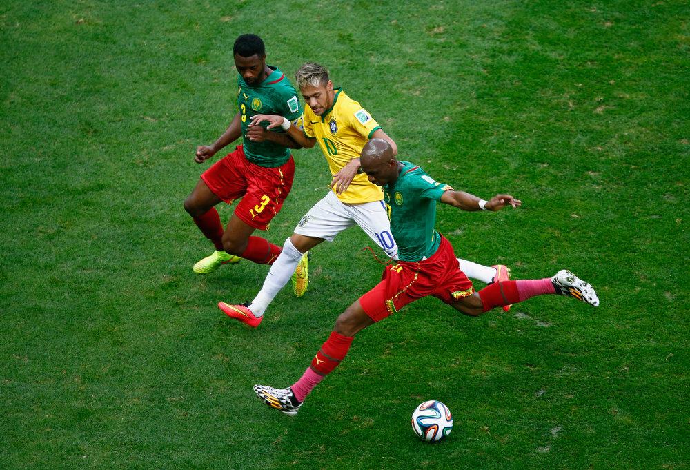 . Neymar of Brazil is challenged by Nicolas N\'Koulou (L) and Stephane Mbia of Cameroon during the 2014 FIFA World Cup Brazil Group A match between Cameroon and Brazil at Estadio Nacional on June 23, 2014 in Brasilia, Brazil.  (Photo by Phil Walter/Getty Images)