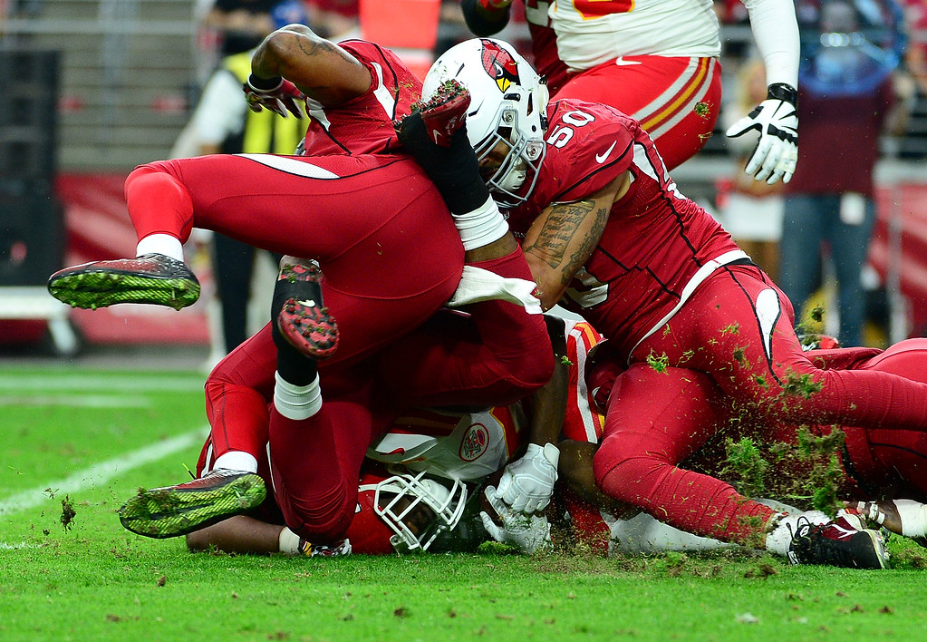 . GLENDALE, AZ - DECEMBER 07: Running back Jamaal Charles #25 of the Kansas City Chiefs is tacked by middle linebacker Larry Foote #50 of the Arizona Cardinals (R) and free safety Rashad Johnson #26 (L) in the first half of the NFL game at University of Phoenix Stadium on December 7, 2014 in Glendale, Arizona.  (Photo by Jennifer Stewart/Getty Images)