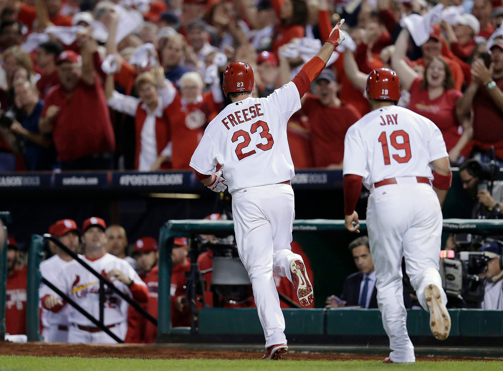 . St. Louis Cardinals\' David Freese (23) runs to the dugout with Jon Jay (19) after Freese drove in Jay with a two-run home run against the Pittsburgh Pirates in the second inning of Game 5 of a National League baseball division series, Wednesday, Oct. 9, 2013, in St. Louis. (AP Photo/Charlie Riedel)