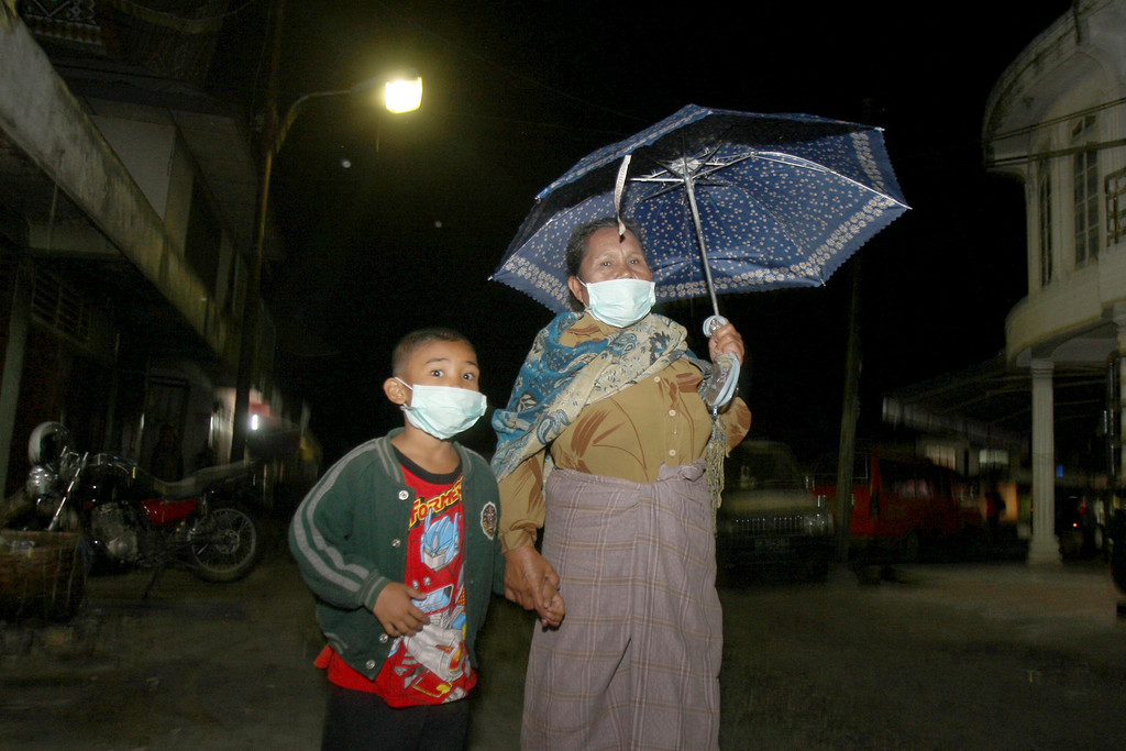 . Villagers wear mask to protect themselves from volcanic ash from the eruption of Mount Sinabung that fall in Tiga Nderket village, North Sumatra, Indonesia, Monday Nov. 4, 2013.  The 2,600-meter (8,530-foot) high volcano has been erupting since Sunday, unleashing volcanic ash high into the sky and forcing the evacuation of villagers living around its slope. (AP Photo/Binsar Bakkara)