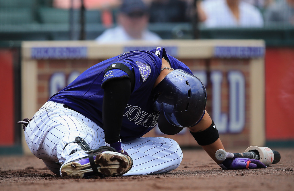 . Carlos Gonzalez #5 of the Colorado Rockies falls to the ground after being hit in the leg while on deck by a foul ball by Jordan Pacheco #15 of the Colorado Rockies in the first inning against the Washington Nationals at Coors Field on June 13, 2013 in Denver, Colorado. Gonzalez was forced to leave the game.  (Photo by Doug Pensinger/Getty Images)