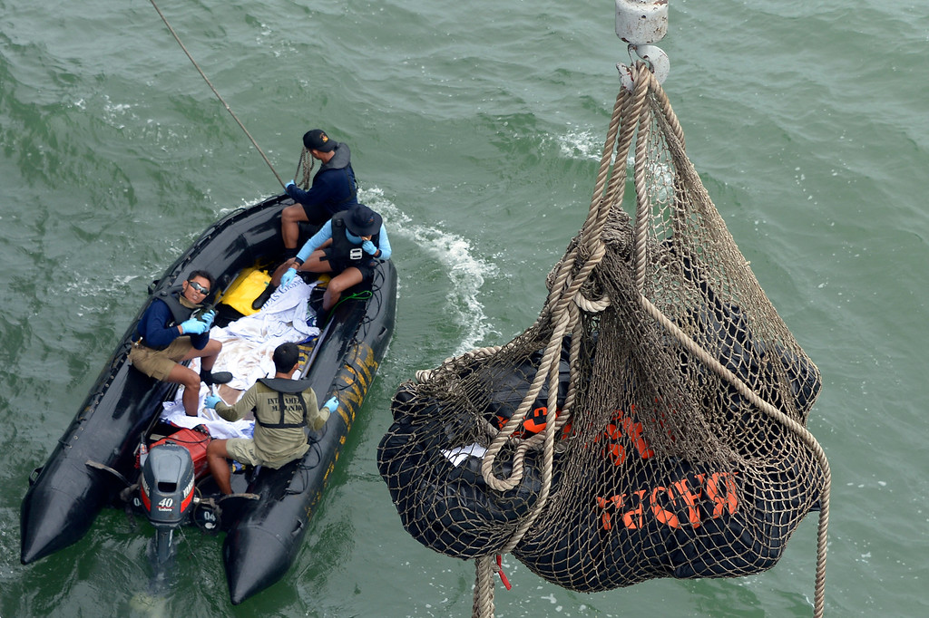 . Bags containing dead bodies of the passengers of AirAsia Flight 8501 are lifted to Indonesian navy vessel KRI Banda Aceh at sea off the coast of Pangkalan Bun, Indonesia, Saturday, Jan. 3, 2015. Indonesian officials were hopeful Saturday they were honing in on the wreckage of AirAsia Flight 8501 after sonar equipment detected two large objects on the ocean floor, a full week after the plane went down in stormy weather. (AP Photo/Adek Berry,Pool)