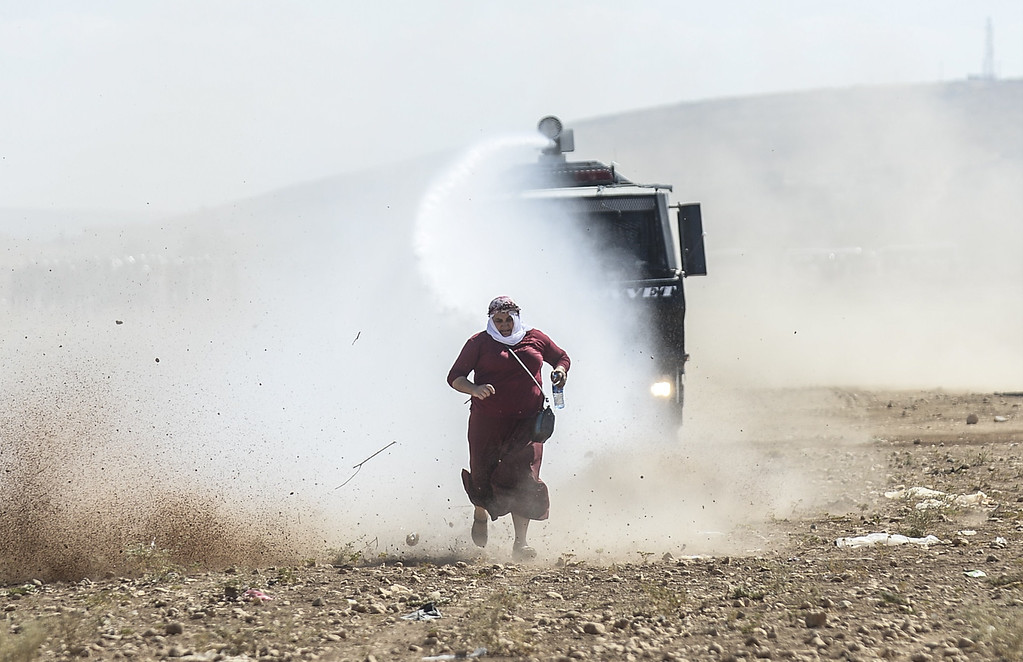 . A Kurdish woman runs away from a water cannon near the Syrian border after Turkish authorities temporarily closed the border at the southeastern town of Suruc in Sanliurfa province, on September 22, 2014. BULENT KILIC/AFP/Getty Images