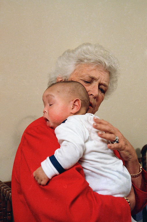 . First lady Barbara Bush holds an infant identified as Donavan during a visit to Grandma\'s House in Washington, March 22, 1989. Grandma\'s House serves as a house for infants and small children infected with the AIDS virus. (AP Photo/Dennis Cook)
