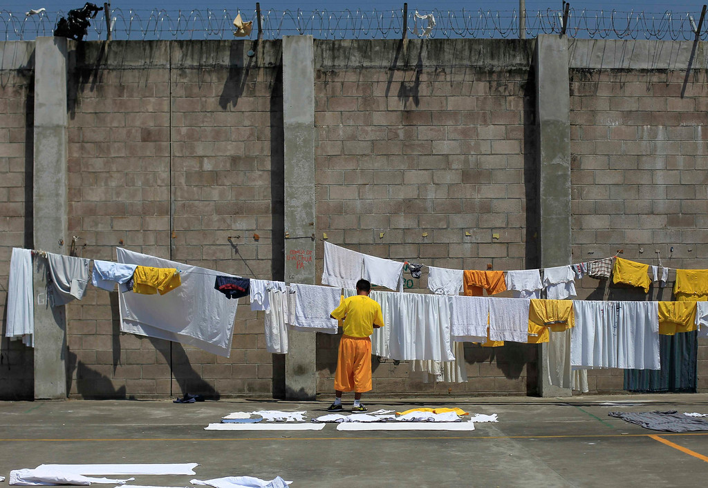 . A jailed gang member hangs up laundry at the maximum security jail of Izalco in Sonsonate March 5, 2013. Jailed members of the country\'s two most powerful gangs MS-13 and the 18th Street gang (Mara 18), members of civic organizations and Bishop Fabio Colindres celebrated mass to mark the first anniversary since the two gangs signed a truce in March 2012 in an effort to reduce violent crimes in the country.        REUTERS/Ulises Rodriguez