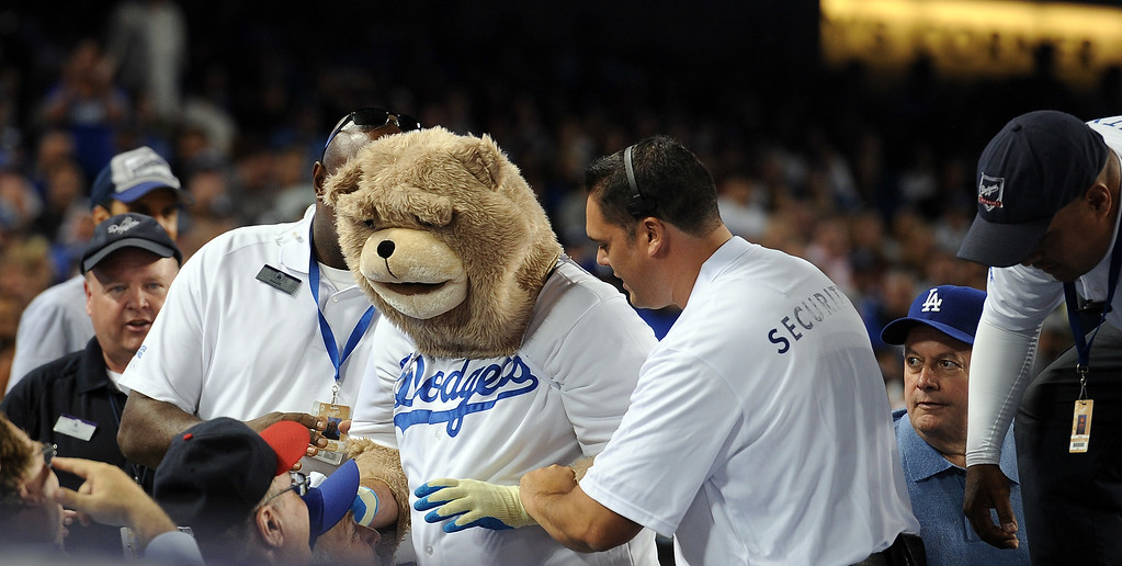 . Dodger security takes away a person dressed as a monkey after they jumped on top if the Cardinals\' dugout and started dancing during game 3 of the NLCS at Dodger Stadium Monday, October 14, 2013. The Dodgers beat the Cardinals 3-0. (Photo by Hans Gutknecht/Los Angeles Daily News)