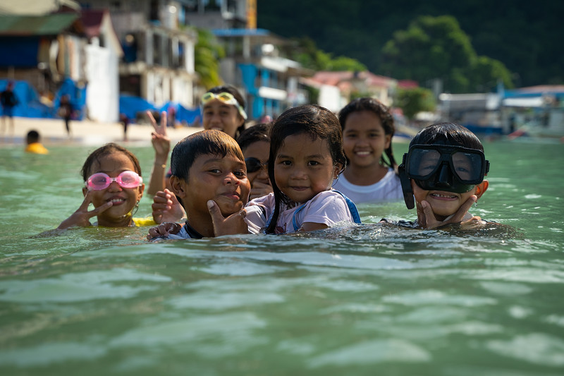 Local children play in the water alonside the tourist-filled beach.