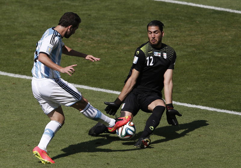 . Argentina\'s forward Gonzalo Higuain (L) fails to get the ball past Iran\'s goalkeeper Alireza Haqiqi during the Group F football match between Argentina and Iran at the Mineirao Stadium in Belo Horizonte during the 2014 FIFA World Cup in Brazil on June 21, 2014. (ADRIAN DENNIS/AFP/Getty Images)