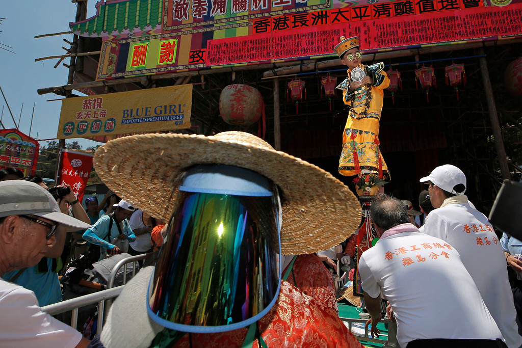 . A child dressed in a traditional Chinese costume floats in the air, supported by a rig of hidden metal rods, during a parade on the outlying Cheung Chau island in Hong Kong to celebrate the Bun Festival Tuesday, May 22, 2018. Thousands of local residents and tourists flocked to an outlying island in Hong Kong to celebrate a local bun festival on Tuesday despite the recording-breaking heat.  The festival features a parade with children dressed as deities floated on poles. Later on Tuesday, contestants will take part in bun-scrambling competition. They will race up a 14-meter bamboo tower to snatch as many plastics buns as possible. Buns that are higher up are worth more points.  (AP Photo/Kin Cheung)