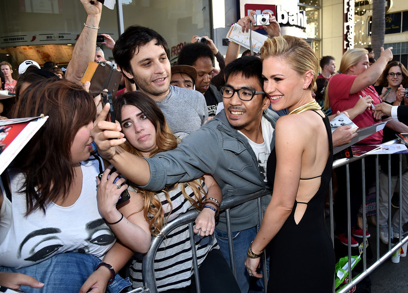 """. Anna Paquin, right, takes a photo with fans as she arrives at the Los Angeles premiere of the 7th and final season of \""""True Blood\"""" at the TCL Chinese Theatre on Tuesday, June 17, 2014. (Photo by John Shearer/Invision/AP)"""