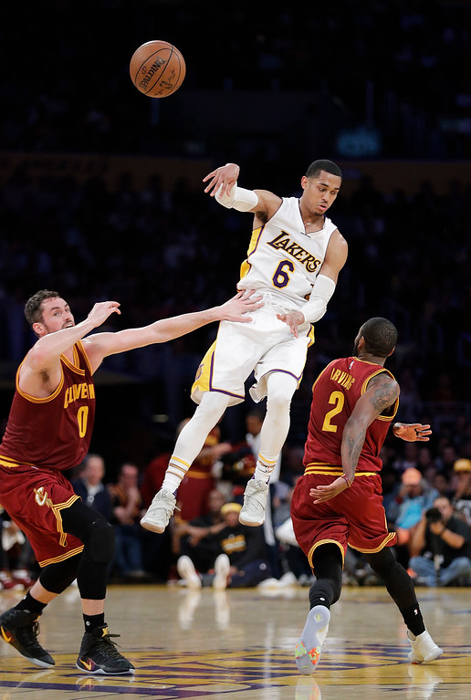. Los Angeles Lakers\' Jordan Clarkson, center, passes the ball as Cleveland Cavaliers\' Kevin Love, left, and Kyrie Irving defend during the first half of an NBA basketball game Sunday, March 19, 2017, in Los Angeles. (AP Photo/Jae C. Hong)
