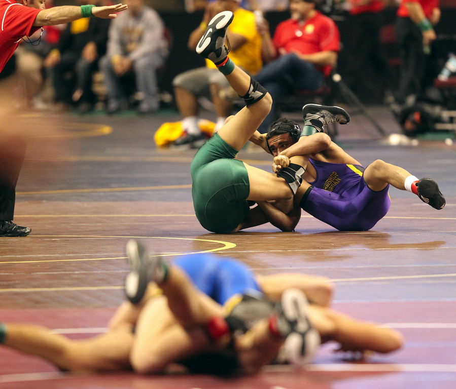 . Riordan\'s Zac Contreras, right, wrestles De La Salle\'s Payton Russom in a 145-pound third round match during the California Interscholastic Federation wrestling championships in Bakersfield, Calif., on Friday, March 1, 2013. Contreras would go onto win. (Anda Chu/Staff)