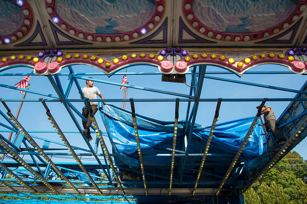 09/11/19 Wesley Bunnell | StaffrrCarnival workers assemble attractions ahead of the Berlin Fair taking place this weekend. Workers climb the beams on the Himalaya ride to attach a tarp covering over the roof beams.