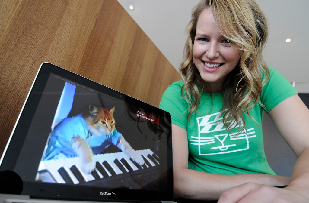 """. FILE - In this Wed., Aug. 29, 2012 file photo, Katie Hill, a program associate with the Walker Art Center, shows a frame from a cat video of a cat playing the piano, in Minneapolis. The Walker presented its  first \""""Internet Cat Video Film Festival\"""" to showcase the best in filmed feline hijinks that drew a crowd of more than 10,000 people. 80 videos culled from 10,000 submissions that covered the simple, funny moment to polished animations and kitty works made by trained filmmakers were shown to the public for free. (AP Photo/Jim Mone, File)"""