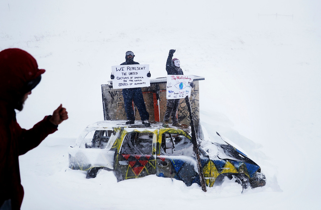 . Demonstrators stand atop a damaged vehicle from a previous protest during a march with military veterans and Native American tribal elders to a closed bridge across from the Dakota Access oil pipeline site in Cannon Ball, N.D., Monday, Dec. 5, 2016. (AP Photo/David Goldman)