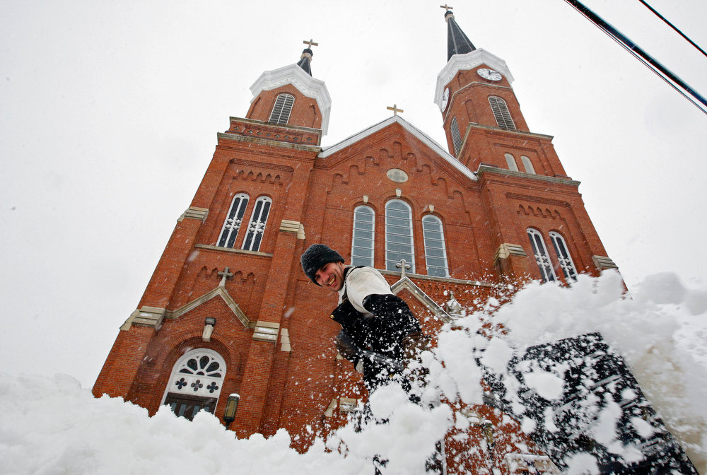 . Keith Kunde clears snow from Sacred Heart Church in Dubuque, Iowa, after the area received several inches of snow on Tuesday, March 5, 2013.  (AP Photo/The Telegraph Herald, Mike Burley)