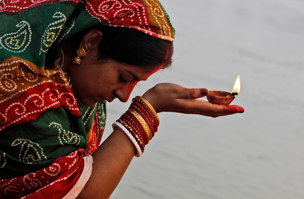 . A Hindu devotee holds a lamp and offers prayers in the Kathajodi River during Chhath Puja festival near Cuttack, India, Friday, Nov. 8, 2013.  (AP Photo/Biswaranjan Rout)