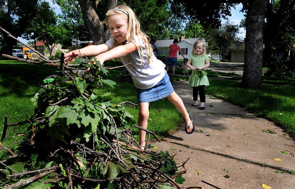 . Caelyn Hippen, 6, left, and her sister Lael, 5, help their father, Chase Hippen, pick up debris around the yard on Saturday afternoon after a storm hit Bohland Avenue in the Highland Park neighborhood. (Pioneer Press: Sherri LaRose-Chiglo)