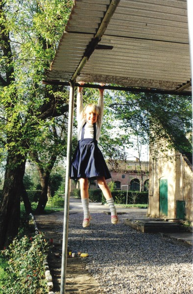 Girl hanging from carport roof, Attock City, Pakistan, 1990s.jpg