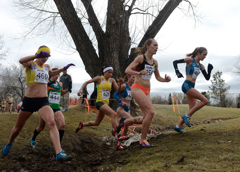 . Amy Van Alstine, right, leads Jennifer Simpson over a creek bed during the Open Women\'s 8K USA Cross Country Championship at the Flatirons Golf Course Saturday afternoon, February 15, 2013. Amy Van Alstine went on to win the championship, Simpson took second. (Photo By Andy Cross / The Denver Post)