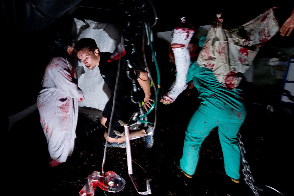 """. Participants rush through a destroyed medical section during one of Britain\'s biggest horror events, the \""""Zombie Evacuation Race\"""" at Carver Barracks near Saffron Walden, England, on October 5, 2013. The race sees thousands of participants attempt to complete a gruelling 5 kilometre cross-country run, while evading \""""zombies\"""", intent on snatching the three life-line strips hanging from every runner\'s waist.  Those who manage to get through with any strips remaining are named as survivors while those without take home an \""""infected\"""" badge.  LEON NEAL/AFP/Getty Images"""
