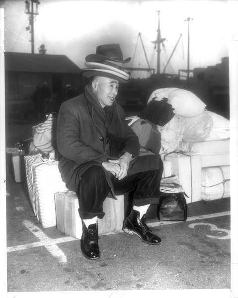 """""""Plenty of Hats -- S. Ichinose, one of 676 Japanese who have elected to quit United States for repatriation to Japan, wears four hats at once.  He didn't want to leave anything behind, carrying all his possessions aboard ship.""""--caption on photograph"""