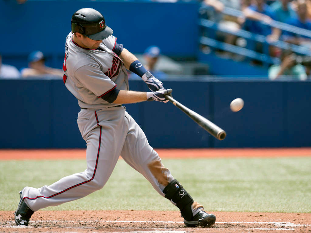 . Minnesota Twins\' Brian Dozier connects for a three-run home run off Toronto Blue Jays starting pitcher R.A. Dickey in the seventh inning. (AP Photo/The Canadian Press, Frank Gunn)