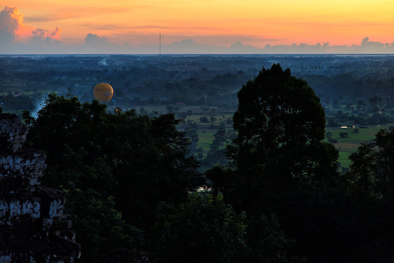 A hot air balloon floats over the fields in front of Phnom Bakheng.