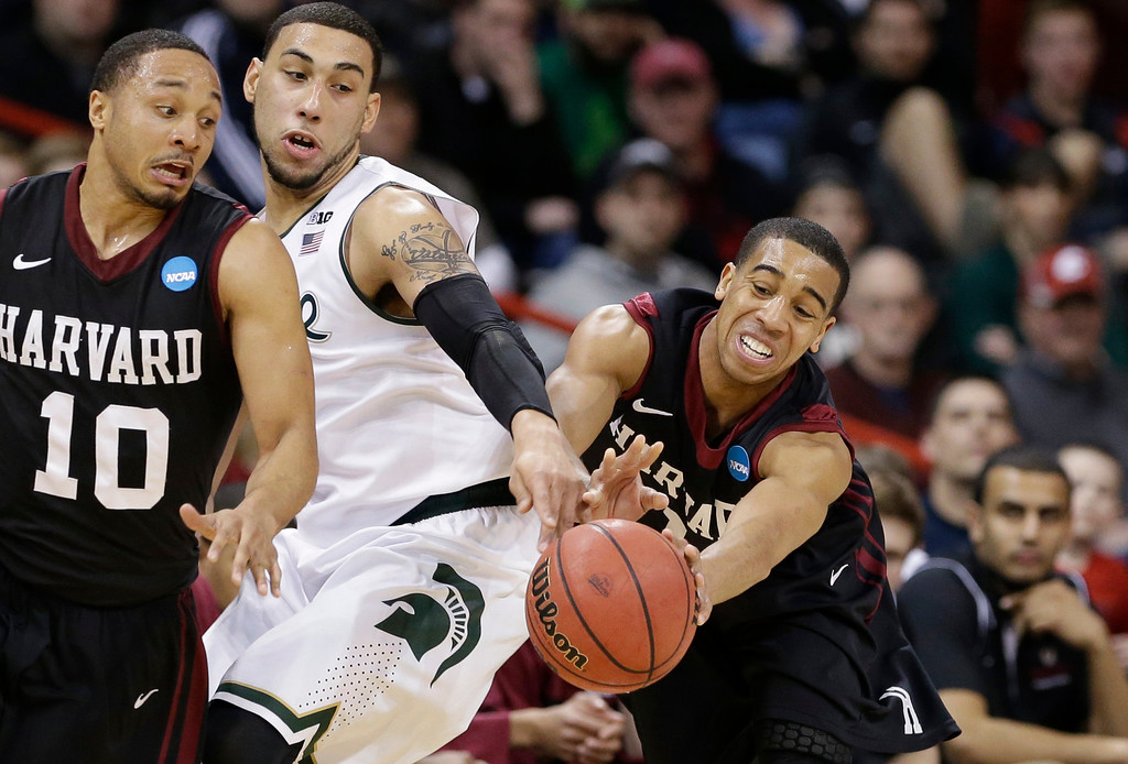 . Harvard\'s Siyani Chambers, right, reaches for the ball as teammate Brandyn Curry (10) and Michigan State\'s Denzel Valentine look on in the second half during the third round of the NCAA men\'s college basketball tournament in Spokane, Wash., Saturday, March 22, 2014. Michigan State won 80-73. (AP Photo/Elaine Thompson)