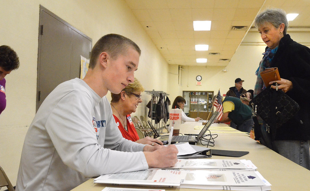 . Luke Peterson, 17, a senior at the International Academy, works as an inspertor at Precinct 1 in the Waterford Parks and Recreation building.    Tuesday, November 4, 2014.  Tim Thompson-The Oakland Press