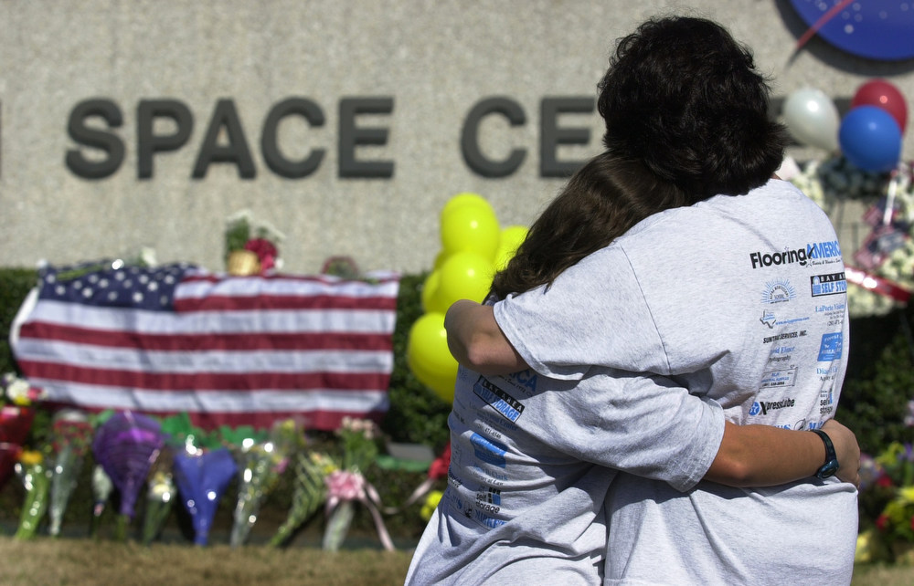 . Kathy Kirsh, right, and her daughter Michelle Eggebrecht, from Seabrook, Texas, console each other outside the Lyndon B. Johnson Space Center in Clear Lake, Texas, Saturday, Feb.1, 2003.  Hundreds of people came to the Johnson Space Center to leave flowers in remembrance of the crew of the space shuttle Columbia. Space shuttle Columbia broke apart in flames 200,000 feet over Texas on Saturday, killing all seven astronauts just minutes before they were to glide to a landing in Florida. (AP Photo/Dallas Morning News, Jim Mahoney)