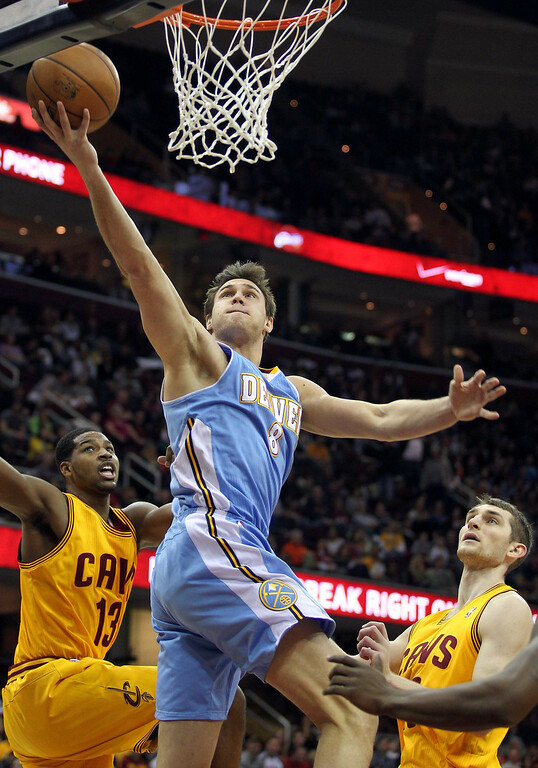 . Denver Nuggets Danilo Gallinari (8) lays the ball in between Cleveland Cavaliers defenders Tristan Thompson (13) and Tyler Zeller during the first quarter of their NBA basketball game in Cleveland, February 9, 2013.  REUTERS/Aaron Josefczyk