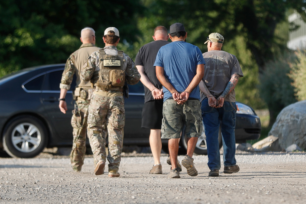 . Government agents take suspects in custody during an immigration sting at Corso\'s Flower and Garden Center, Tuesday, June 5, 2018, in Castalia, Ohio. The operation is one of the largest against employers in recent years on allegations of violating immigration laws.  (AP Photo/John Minchillo)