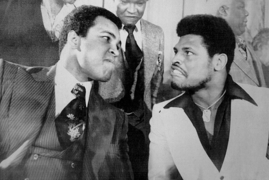 . Hyping Next Title Defense -- Muhammad Ali, the world heavyweight champion, left, strains to stare down a grimacing Leon Spinks, the Olympic heavyweight champion, during a news conference Thursday to promote their Feb. 15 title bout in Las Vegas. It was announced Thursday that Ali has signed a $12 million contract to defend his championship next September against Ken Norton. 1977. Credit: AP Laserphoto