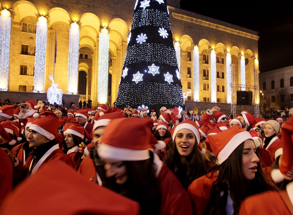 . Georgian Santa Clauses greet children in front of the former Parliament building decorated with a Christmas tree in Tbilisi, Georgia, 25 December 2013.  EPA/ZURAB KURTSIKIDZE