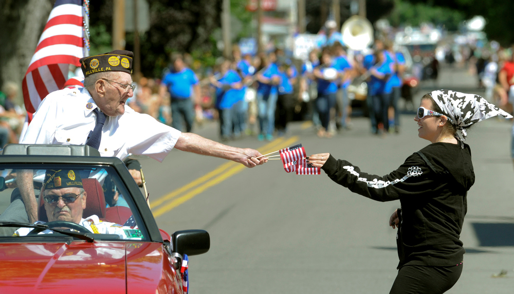 Description of . John Eifert of the Millville American Legion, left, hands out flags to people lining North State Street while riding in the annual Fourth of July P2arade in Millville, Pa., Friday, July 4, 2014. (AP Photo/Bloomsburg Press Enterprise, Jimmy May)
