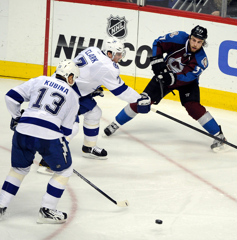 . Ryan O\'Reilly, Colorado Avalanche, passes the puck across ice against Brett Clark, #7, and Pavel Kubina, Tampa Bay Lighting, in the second period of play  at Pepsi Center Friday evening. Av\'s win 2-1. Andy Cross, The Denver Post