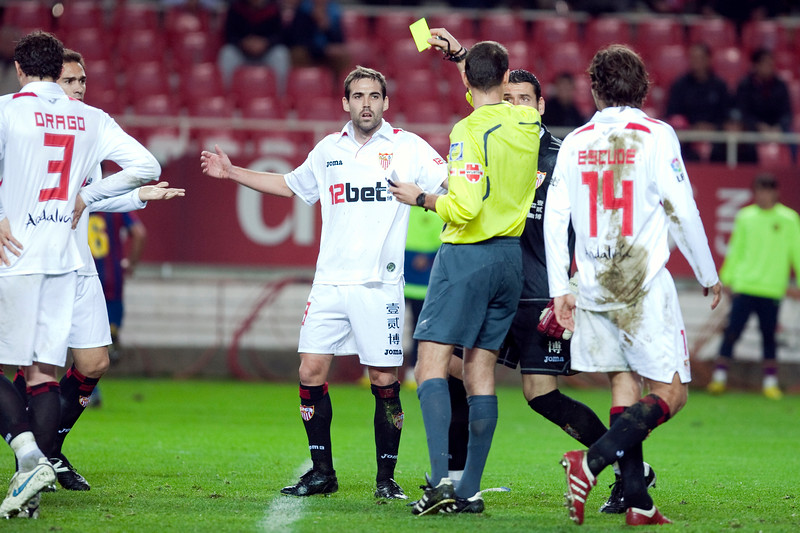 The referee showing a yellow card to Fernando Navarro. Spanish Cup game between Sevilla FC and FC Barcelona, Ramon Sanchez Pizjuan stadium, Seville, Spain, 13 January 2010