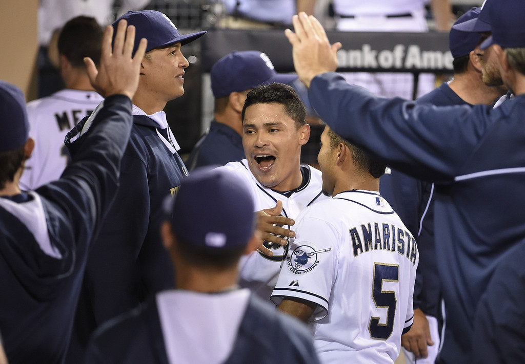. SAN DIEGO, CA - APRIL 16:  Everth Cabrera #2 of the San Diego Padres, center, is congratulated by Alexi Amarista #5 after scoring during the fifth inning of a  baseball game against the Colorado Rockies at Petco Park April 16, 2014 in San Diego, California.  (Photo by Denis Poroy/Getty Images)