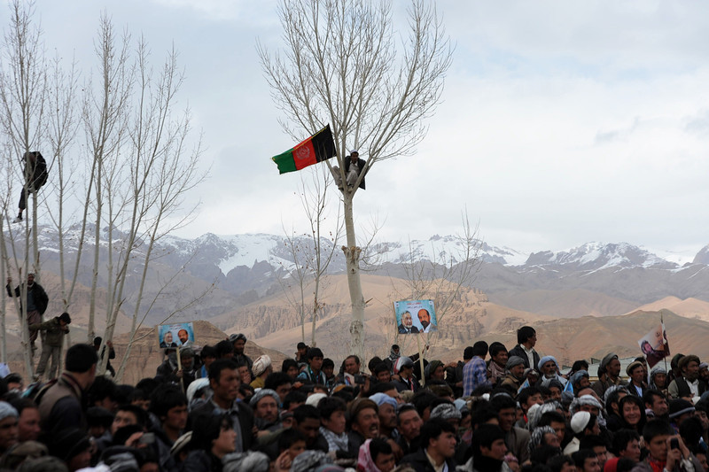 . An man holds an Afghan flag as he watches a political rally from atop a tree during a campaign stop by Presidential candidate Zalmai Rassoul in Bamiyan on April 1, 2014.  Afghanistan will vote on April 5 to choose a successor to President Hamid Karzai and to decide the make-up of 34 provincial councils in elections seen as a benchmark of progress since the Taliban were ousted from power in 2001. Eight candidates are running in the April 5 presidential election, with a second round run-off between the two leading contenders expected in late May.  (Hashmatullah/AFP/Getty Images)