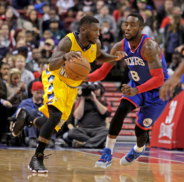 . Denver Nuggets\' Nate Robinson, left, drives against Philadelphia 76ers\' Tony Wroten (8) in the first half of an NBA basketball game Saturday Dec. 7, 2013, in Philadelphia.  (AP Photo/H. Rumph Jr)