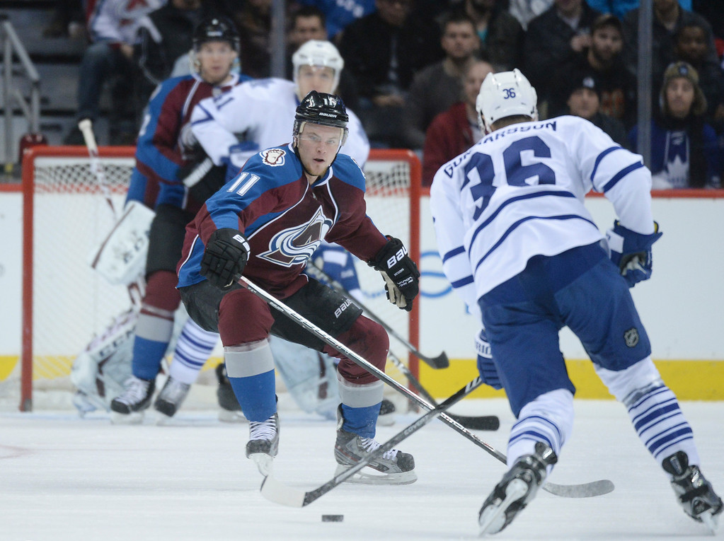 . DENVER, CO. - JANUARY 21:  Avalanche wing Jamie McGinn (11) tried to stop Toronto defenseman Carl Gunnarsson (36) in the first period. The Colorado Avalanche hosted the Toronto Maple Leafs Tuesday night, January 21, 2014 at the Pepsi Center. Photo By Karl Gehring/The Denver Post