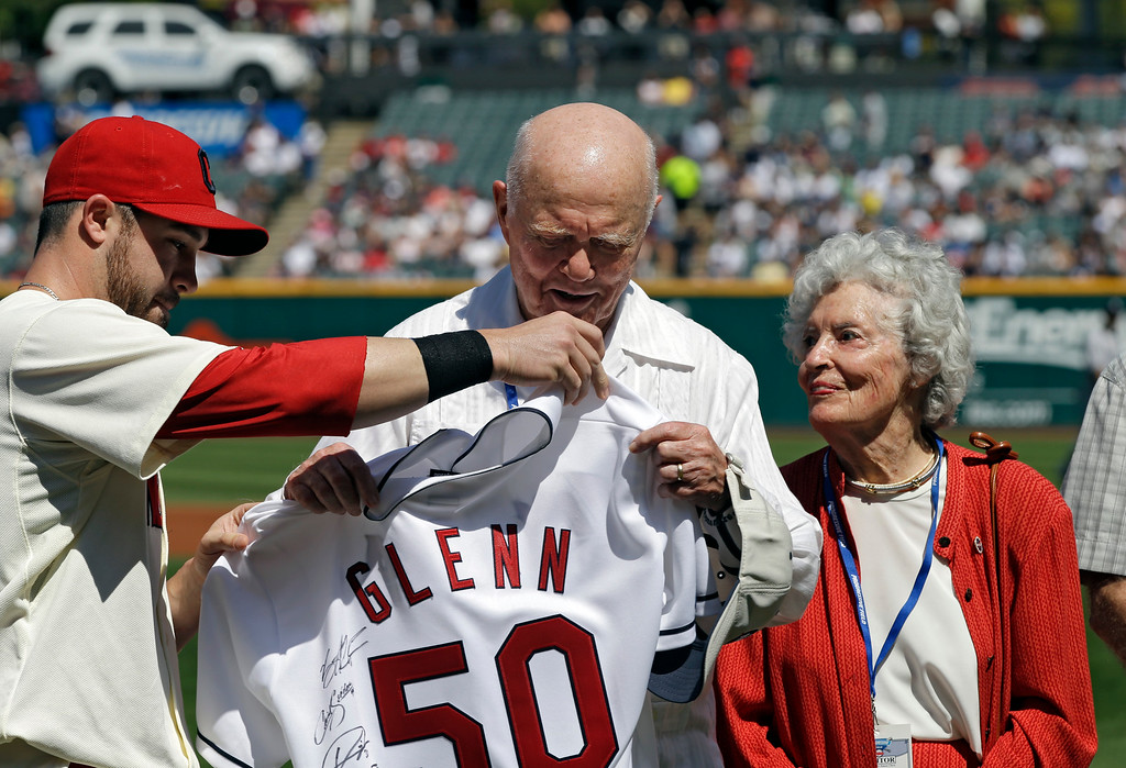 . Former astronaut and senator John Glenn, center, receives a signed jersey from Cleveland Indians second baseman Jason Kipnis as Annie Glenn looks on before a baseball game between the Indians and the New York Yankees Sunday, Aug. 26, 2012, in Cleveland. (AP Photo/Mark Duncan)