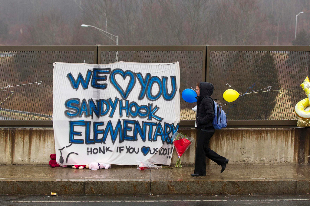 . A woman walks over a freeway overpass near a memorial for the victims of the recent shooting in Sandy Hook Village in Newtown, Connecticut, December 16, 2012. Twelve girls, eight boys and six adult women were killed in a shooting on Friday at Sandy Hook Elementary School in Newtown.  REUTERS/Lucas Jackson