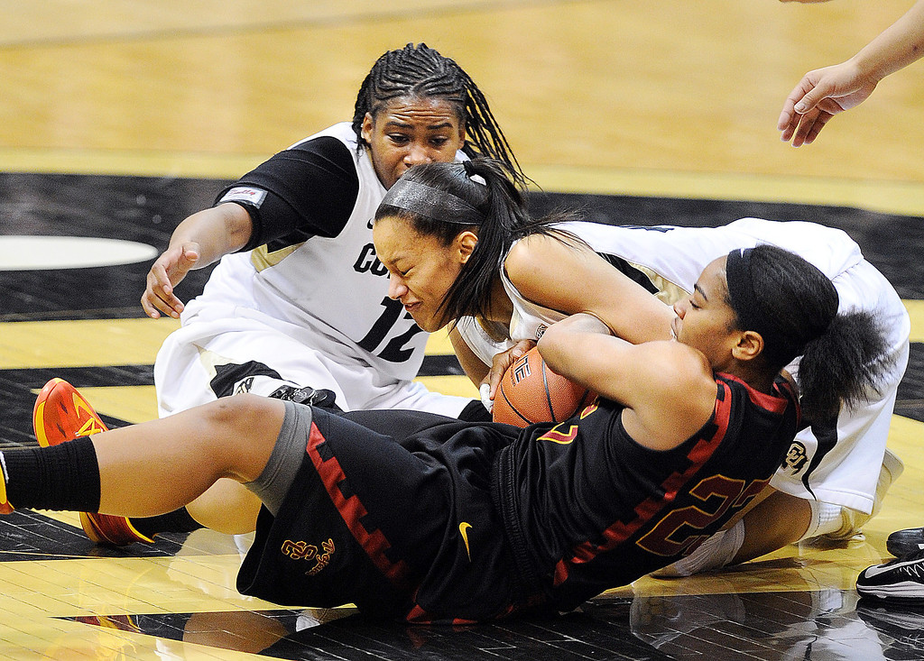 . Colorado\'s Ashley Wilson (12) and Arielle Roberson struggle for the ball with Southern California\'s Brianna Barrett during the second half of an NCAA college basketball game on Sunday, March 2, 2014, in Boulder, Colo. (AP Photo/Daily Camera, Cliff Grassmick) NO SALES