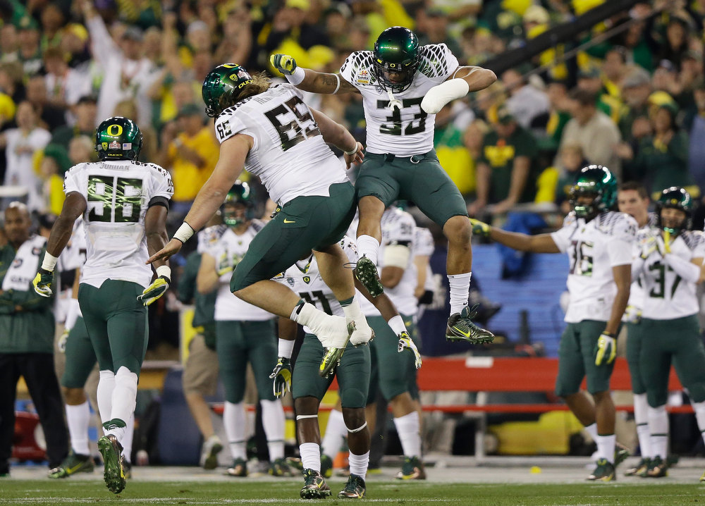 . Isaac Remington #65 and Tyson Coleman #33 of the Oregon Ducks celebrate stopping the Kansas State Wildcats on a fourth down in the first quarter of the Tostitos Fiesta Bowl at University of Phoenix Stadium on January 3, 2013 in Glendale, Arizona.  (Photo by Ezra Shaw/Getty Images)