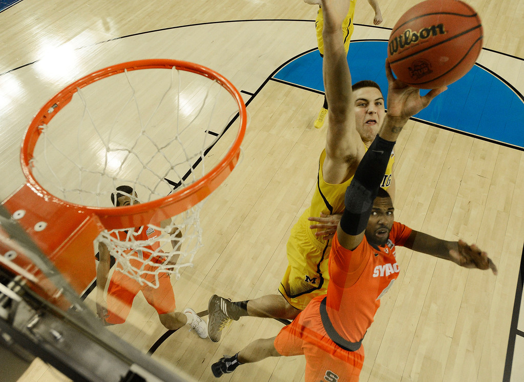 . Syracuse\'s Nolan Hart (4) shoots against Michigan\'s Mitch McGary (4) during the first half of the NCAA Final Four tournament college basketball semifinal game Saturday, April 6, 2013, in Atlanta. (AP Photo/NCAA Photos, Chris Steppig, Pool)