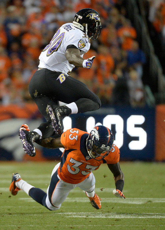 . Baltimore Ravens running back Bernard Pierce (30) leaps over Denver Broncos safety Duke Ihenacho (33) in the first quarter.  (Photo by John Leyba/The Denver Post)